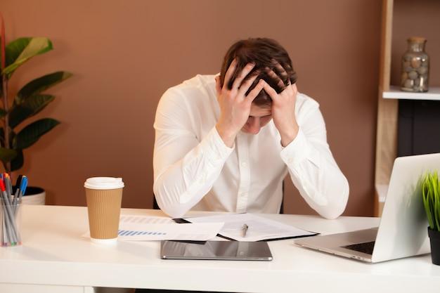 Hombre de negocios joven frustrado que trabaja en la computadora portátil en la oficina