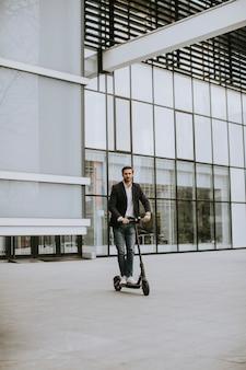 Hombre de negocios joven guapo en ropa casual montando un scooter eléctrico por un edificio de oficinas en una reunión de negocios