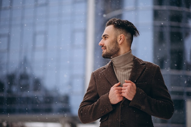 Hombre de negocios joven hermoso afuera en invierno