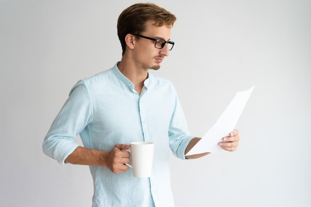 Hombre de negocios joven hermoso concentrado que analiza informe y que bebe el café.