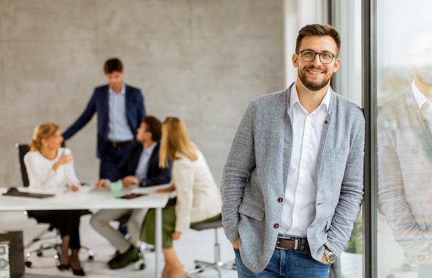 Hombre de negocios joven hermoso que confía en la oficina delante de su equipo