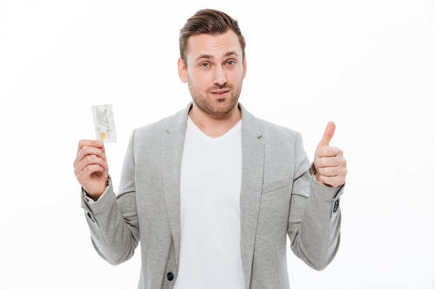 Hombre de negocios joven hermoso que muestra los pulgares para arriba que sostienen la tarjeta de crédito.