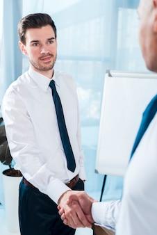 Hombre de negocios joven hermoso que sacude la mano con su socio masculino en la oficina