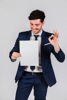 Hombre de negocios joven hermoso que sostiene el libro blanco en la mano que muestra la muestra aceptable contra el contexto gris