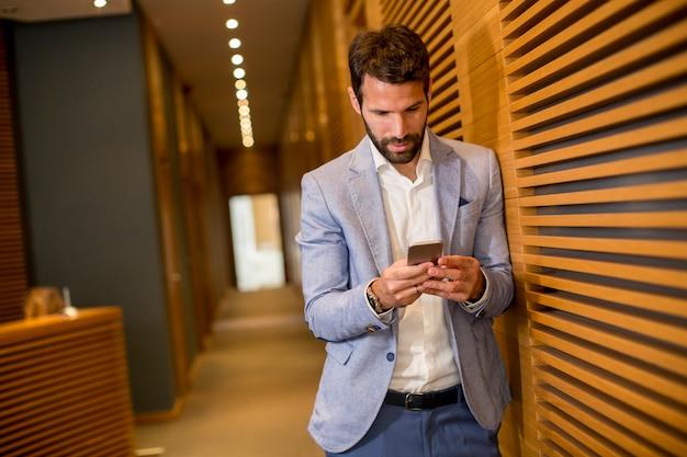 Hombre de negocios joven hermoso que usa el teléfono en oficina