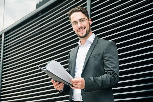 Hombre de negocios joven hermoso sonriente que se coloca fuera de la pared que sostiene la carpeta en la mano