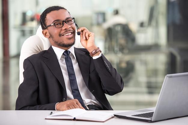 El hombre de negocios joven hermoso está tomando una llamada.