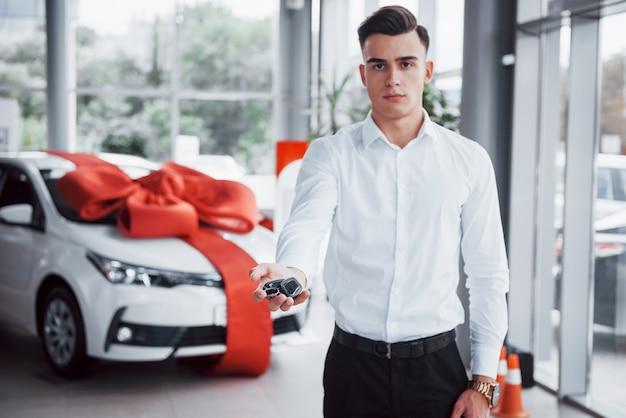 Hombre de negocios joven con llaves en sus manos, compra un coche en la cabina.