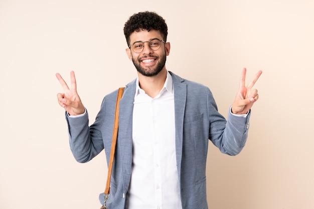 Hombre de negocios joven marroquí aislado en la pared beige mostrando el signo de la victoria con ambas manos