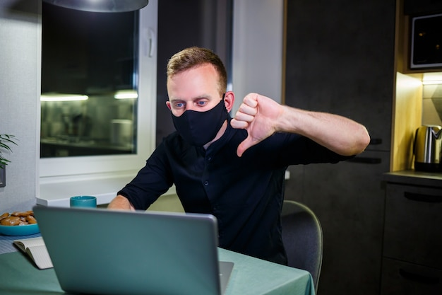 Hombre de negocios joven con una máscara protectora antivirus negra, trabajando en casa, sentado en la mesa de la cocina con una computadora portátil. trabajar desde casa en cuarentena