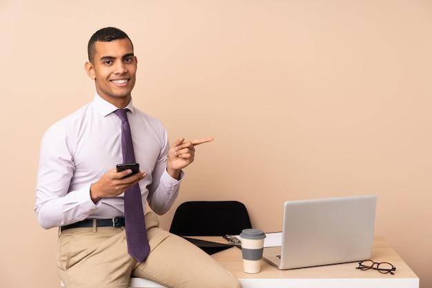 Hombre de negocios joven en una oficina que señala el dedo al lado