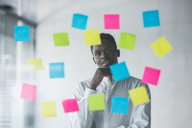 Hombre de negocios joven de pie delante de la pared de cristal de pegatinas y mirando cómo lograr objetivos en su oficina