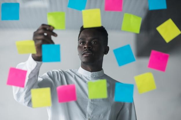 Hombre de negocios joven de pie delante de la pared de vidrio de pegatinas y escribir la tarea en la etiqueta en su oficina