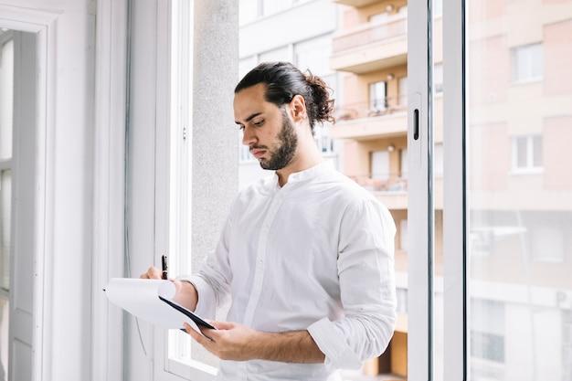 Hombre de negocios joven que se coloca cerca de la escritura de la ventana en la libreta con la pluma