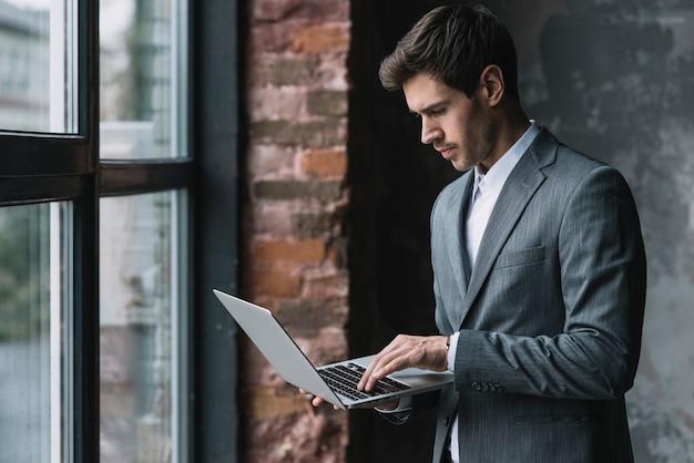 Hombre de negocios joven que se coloca cerca de la ventana usando la computadora portátil