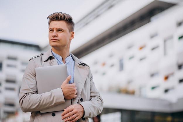 Hombre de negocios joven que se coloca con el ordenador portátil fuera del centro de negocios