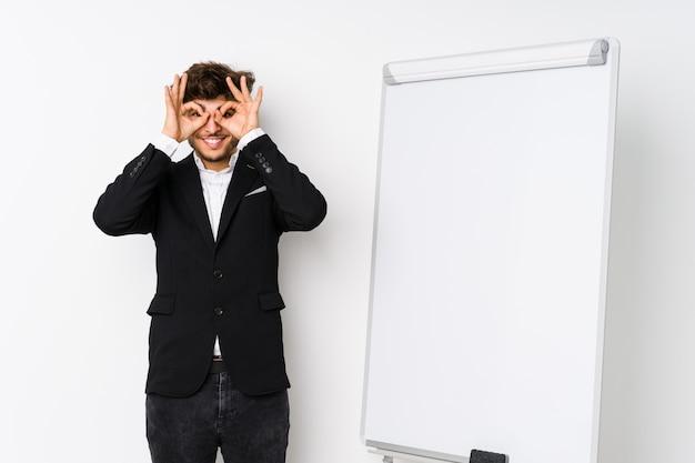 Hombre de negocios joven que entrena al árabe que muestra la muestra aceptable sobre ojos