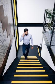 Hombre de negocios joven que habla en el teléfono móvil y que sube en las escaleras en oficina