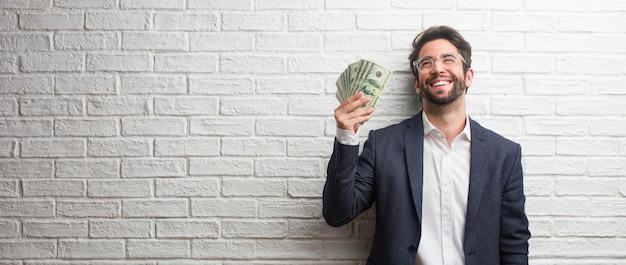 Hombre de negocios joven que lleva un traje contra una pared de ladrillos blanca riendo y divirtiéndose, estar relajado y alegre, se siente seguro y exitoso