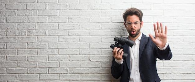 Hombre de negocios joven que lleva un traje contra una pared de ladrillos blanca seria y determinada