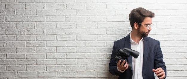 Hombre de negocios joven que lleva un traje contra una pared de ladrillos blanca sorprendida y sorprendida