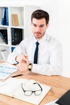 Hombre de negocios joven que mira a la cámara que señala su dedo hacia reloj en el lugar de trabajo