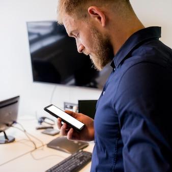Hombre de negocios joven que mira el móvil de la pantalla en blanco