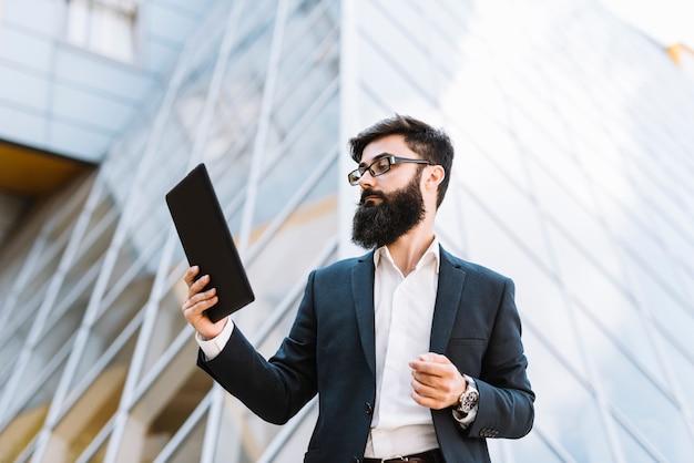 Hombre de negocios joven que mira la tableta digital que se coloca delante del edificio