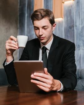 Hombre de negocios joven que mira la tableta