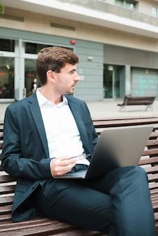 Hombre de negocios joven que se sienta en banco con la computadora portátil