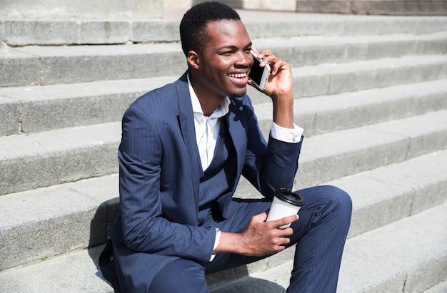 Hombre de negocios joven que se sienta en los pasos que sostienen la taza disponible disponible