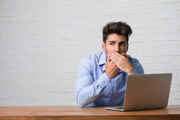 Hombre de negocios joven que se sienta y que trabaja en una boca de la cubierta del ordenador portátil