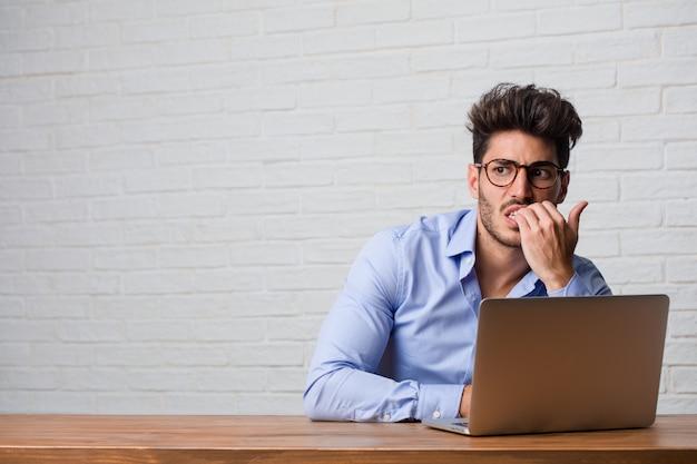Hombre de negocios joven que se sienta y que trabaja en una computadora portátil que muerde clavos