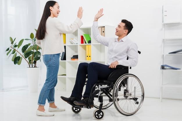 Hombre de negocios joven que se sienta en la silla de ruedas que da el alto-cinco a su colega femenino en la oficina