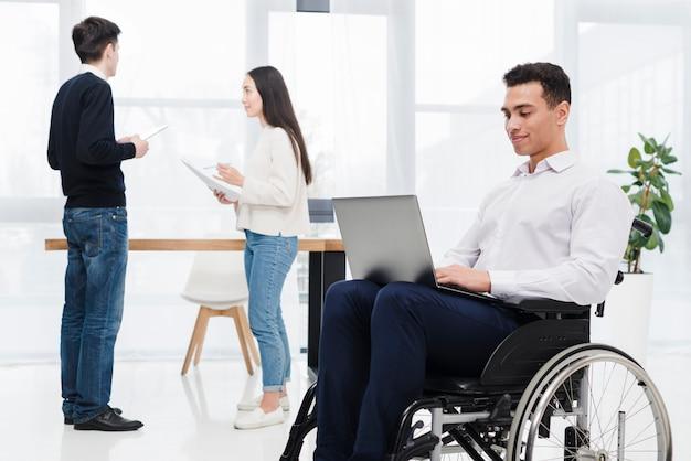 Hombre de negocios joven que se sienta en la silla de ruedas usando el ordenador portátil con su colega que discute algo en el contexto