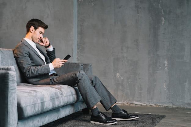 Hombre de negocios joven que se sienta en el sofá gris usando el teléfono móvil