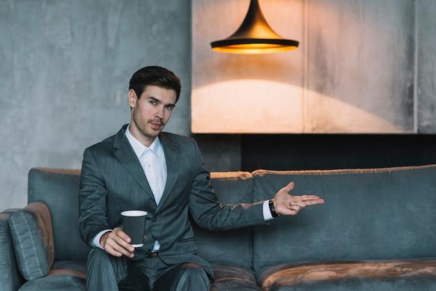 Hombre de negocios joven que se sienta en el sofá que hace gesto del arma de la mano debajo de la lámpara iluminada