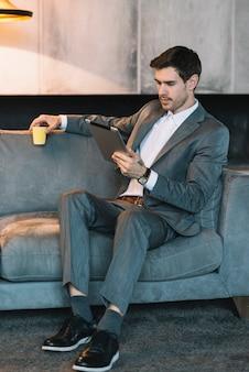 Hombre de negocios joven que se sienta en el sofá que sostiene la taza de café que mira la tableta digital