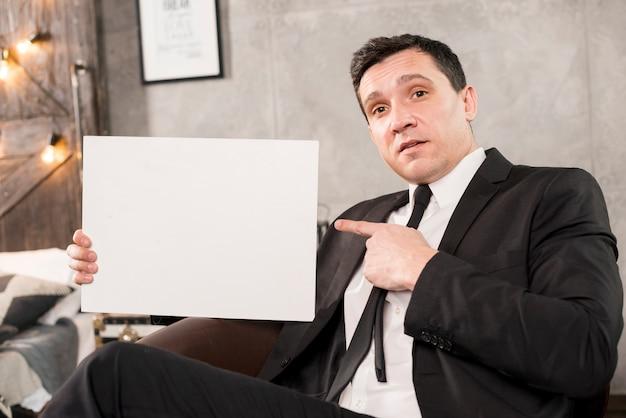Hombre de negocios joven que sostiene el papel en blanco