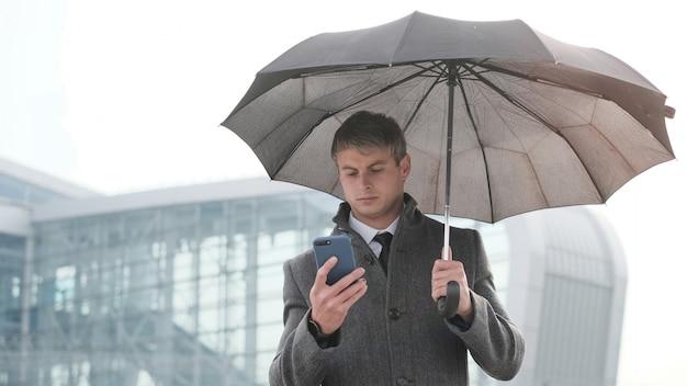 Hombre de negocios joven que sostiene el paraguas y que usa un teléfono elegante en un día lluvioso.
