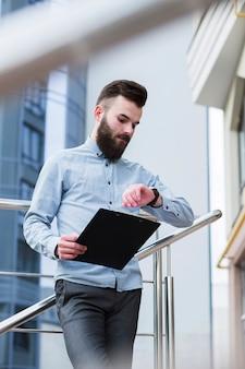 Hombre de negocios joven que sostiene el tablero disponible que comprueba tiempo