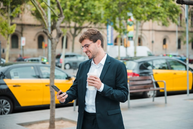 Hombre de negocios joven que sostiene la taza de café que mira el teléfono móvil