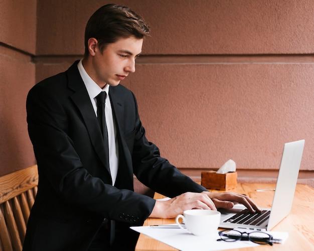 Hombre de negocios joven que trabaja en la computadora portátil
