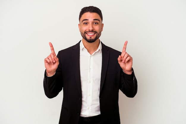 Hombre de negocios joven de raza mixta aislado sobre fondo blanco indica con ambos dedos hacia arriba mostrando un espacio en blanco.