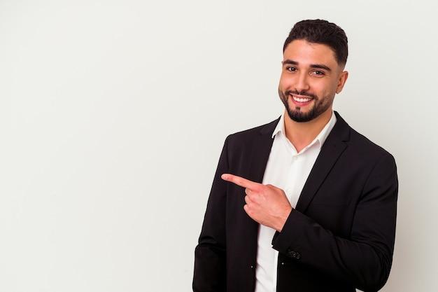 Hombre de negocios joven de raza mixta aislado sobre fondo blanco sonriendo y apuntando a un lado, mostrando algo en el espacio en blanco.