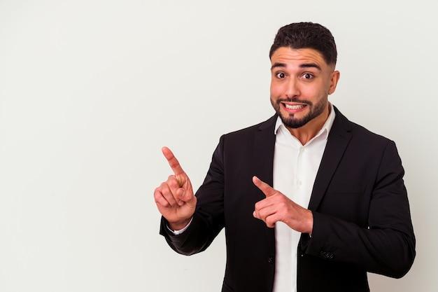 Hombre de negocios joven de raza mixta aislado sobre fondo blanco sorprendido apuntando con los dedos índices a un espacio de copia.