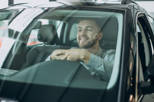Hombre de negocios joven sentado en un coche