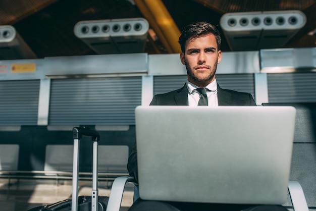 Hombre de negocios joven sentado en la computadora con la maleta en