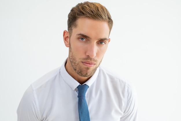 Hombre de negocios joven serio que mira la cámara