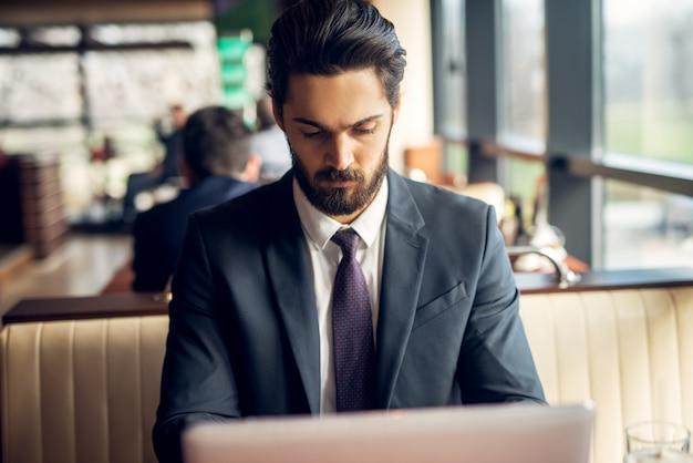 Hombre de negocios joven serio que se sienta en una cafetería y que trabaja en una computadora portátil.